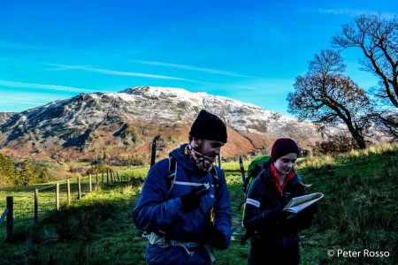 Photo of two walkers looking at a map below a snow covered mountain, on a UBES weekend trip