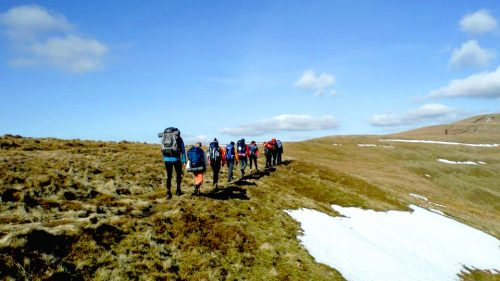 Group walking through a hill side, with blue skies and snow on the ground