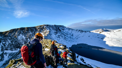 Group descending with helmets on towards a lake after some winter mountaineering