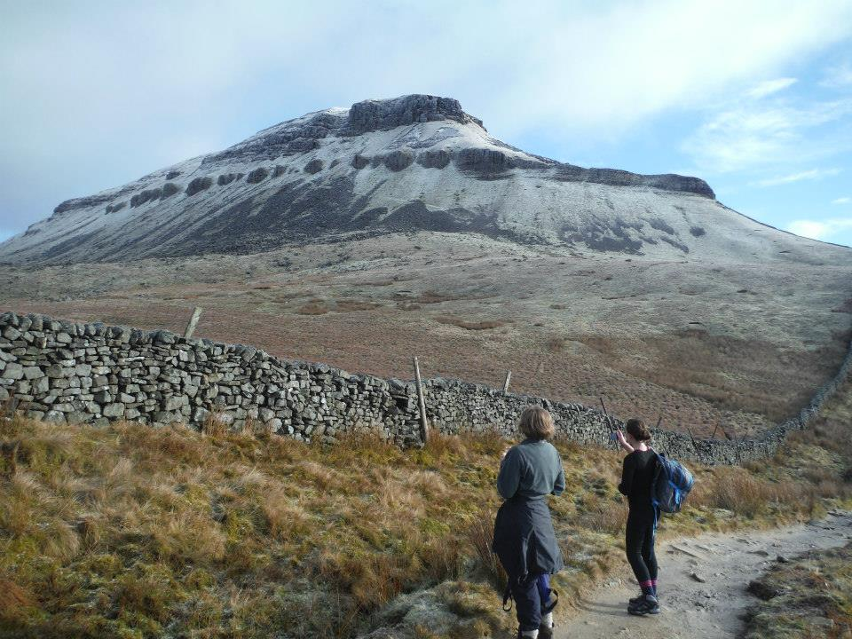 Photo of two walkers approaching the Pen-y-ghent hill, part way through the Yorkshire Dales Three Peaks challenge